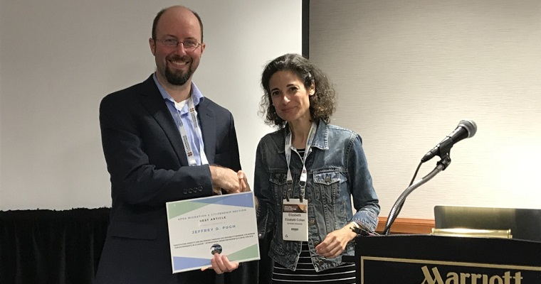 Jeff receiving award at APSA from Dr. Elizabeth Cohen  in August from the president of the migration and citizenship section,