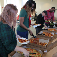 McCormack Graduate School Students grabbing pizza.