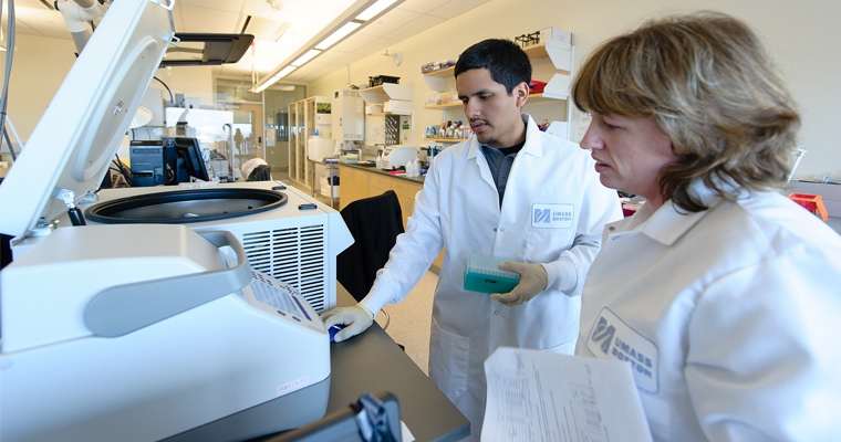 Diego Almanza and Amy Avery work with the equipment in UMass Boston's Genomics Core