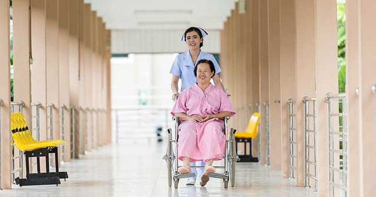 A nurse pushes a patient in a wheelchair down a corridor