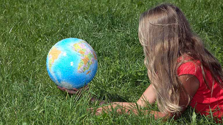 conceptual image girl lying on grass playing with globe