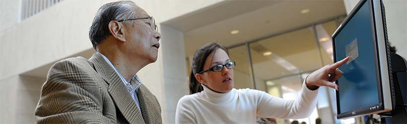 elderly asian man looks on at woman pointing at computer screen