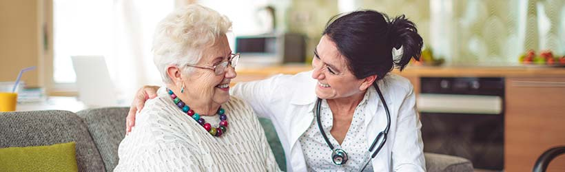 Elderly woman wearing necklace smiling on couch while healthcare worker on right with arm around her